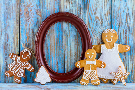 gingerbread man: Still life of gingerbread, gingerbread men, brown frame and pine cone on blue wooden background, Christmas or New Year background, template greeting card