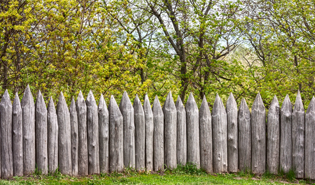 bastion: Defensive wooden palisade stockade from sharpened logs on the background of trees Stock Photo