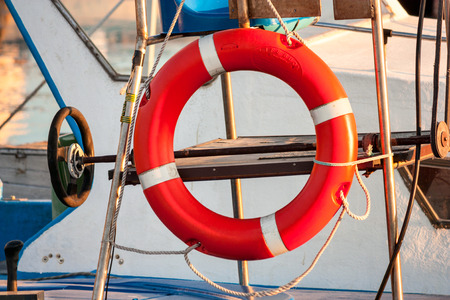 Red lifebuoy, fixed on deck of the yacht, moored in the city marina