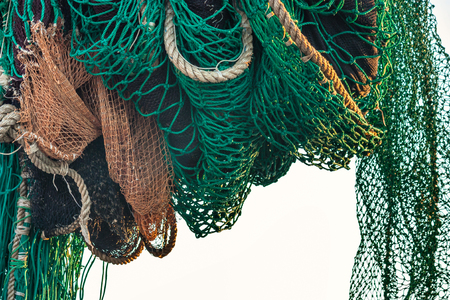 Drying fishing nets on the trawler in city harbor at sunset of the day
