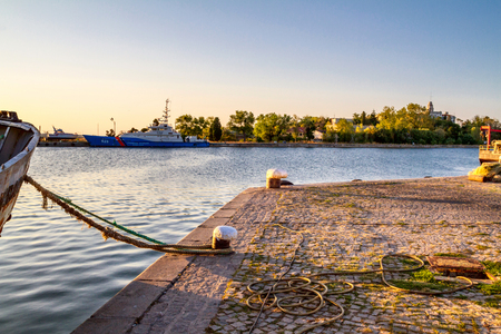 Seaside landscape - view of the pier with a moored ship at sunset time, town of Sozopol on the Black Sea coast in Bulgaria