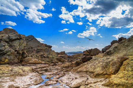 The rocky landscape with gulls under the sky with clouds, seashore near city of Sozopol in Bulgaria Stock Photo