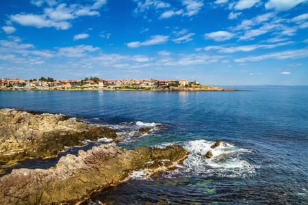 Coastal landscape - the rocky seashore with houses under the sky with clouds, town of Sozopol on the Black Sea coast in Bulgaria
