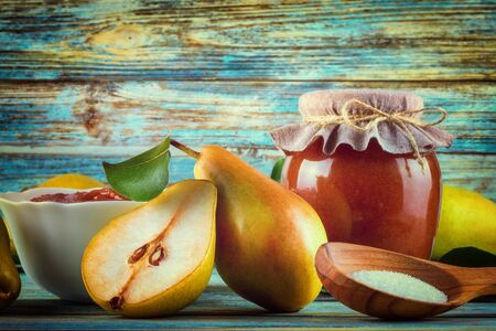 Glass jar of homemade pear jam with fresh fruits and ingredients on woody background