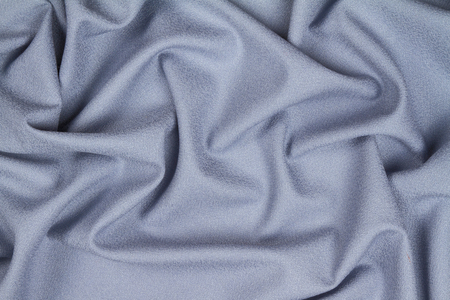 Blue woolen crumpled wrinkled fabric with waves, background crumpled tissue