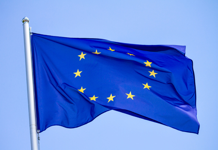 Flag of the European Union waving in the wind on flagpole against the sky on sunny day, close-up