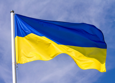 Flag of Ukraine waving in the wind on flagpole against the sky with clouds on sunny day, close-up Stock Photo