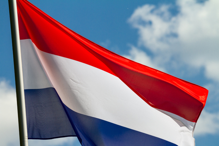 Flag of the Netherlands waving in the wind on flagpole against the sky with clouds on sunny day, close-up Фото со стока