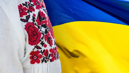 Beautiful Ukrainian embroidery on authentic folk clothes to the background flag of Ukraine, close-up