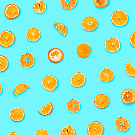 Set of dried slices and half a slice of orange and lemon as background, isolated on blue background