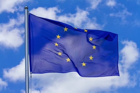Flag of the European Union waving in the wind on flagpole against the sky with clouds on sunny day, close-up Stock Photo - 123592172