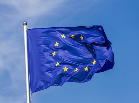 Flag of the European Union waving in the wind on flagpole against the sky with clouds on sunny day, close-up