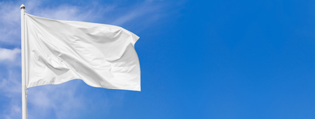 White flag waving in the wind on flagpole against the sky with clouds on sunny day, banner, closeup Stock Photo