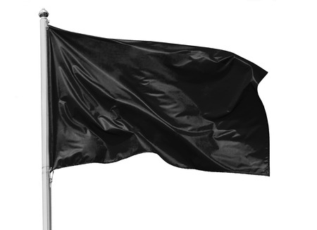Black flag waving in the wind on flagpole, isolated on white background, closeup 免版税图像