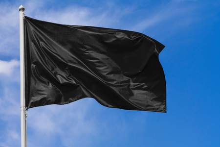 Black flag waving in the wind on flagpole against the sky with clouds on sunny day, closeup