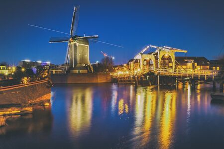 Cityscape - evening view of the city canal with drawbridge and windmill, the city of Leiden, Netherlands