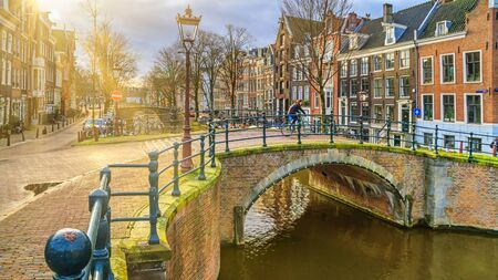 Cityscape on a sunny winter day - view of the bridge and canal in the historic center of Amsterdam, The Netherlands