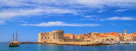 Coastal summer landscape, banner - view of a sailboat and the City Harbour of the Old Town of Dubrovnik on the Adriatic coast of Croatia