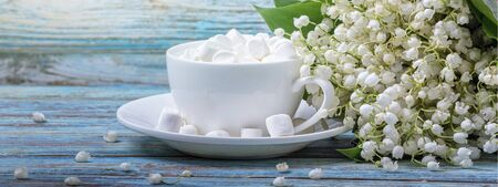 Rural still-life - marshmallows on the background of a bouquet of lilies of the valley, closeup