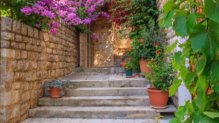 Mediterranean summer cityscape - view of a medieval street with stairs and flowers in the Old Town of Hvar, the island of Hvar, the Adriatic coast of Croatia