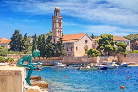 Coastal summer cityscape - view of the monument and the church on the waterfront of the town of Hvar, on the island of Hvar, the Adriatic coast of Croatia