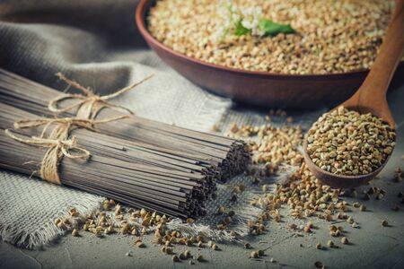 Rural still-life - traditional japanese soba noodles made of buckwheat flour and the peeled groats of buckwheat, on the background of burlap, closeup with selective focus