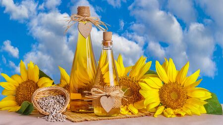 Rural still-life - sunflower oil in glass bottles against the background of the sky with clouds, closeup with space for text