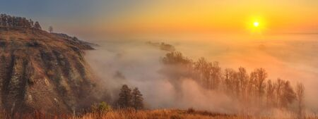 Autumn sunrise landscape, panorama, banner - view of a river valley covered with fog in the light of the sunrays, the northeast of Ukraine Stock Photo