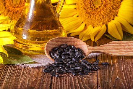 Rural still-life - the sunflower oil in glass cruet with flowers of sunflower (Helianthus annuus) and seeds in a wooden spoon, closeup Stok Fotoğraf