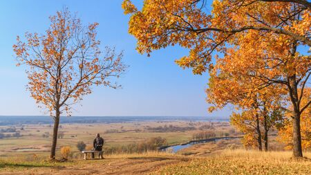 Autumn landscape - view of the hiker sitting on a bench overlooking a river valley on a sunny day, the northeast of Ukraine Stock Photo