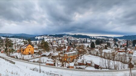 Rural winter landscape - view of the village Vorokhta with the railway in valley Prut River the Carpathian Mountains, in Ukraine Banco de Imagens