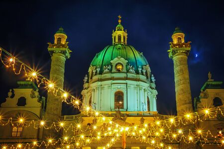 Festive cityscape - view of the Christmas Market on Karlsplatz (Charles Square) and the Karlskirche (St. Charles Church) in the city of Vienna, Austria