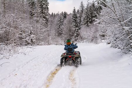 Winter landscape - view of the snowy road with a quad bike in the winter mountain forest after snowfall