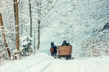 Winter landscape - view of the snowy road with with a horse sleigh in the winter mountain forest after snowfall