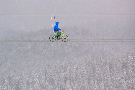 Winter landscape - view of the bike zip line with cyclist above the winter mountain forest during a snowfall, Bukovel ski resort, Carpathian mountains, Ukraine, 18 January, 2019 Stock fotó