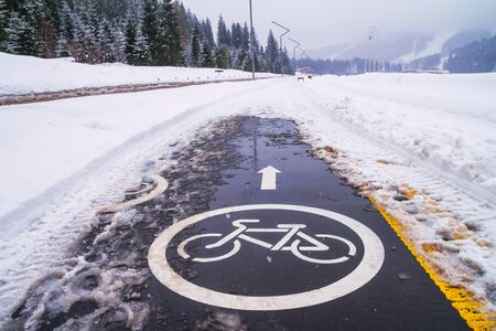 Winter landscape - view of the snowy bike path near the ski resort after snowfall