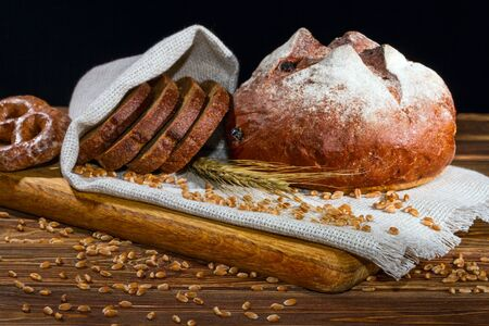 Still-life with fresh bread on sackcloth on black background, with space for text, selective focus