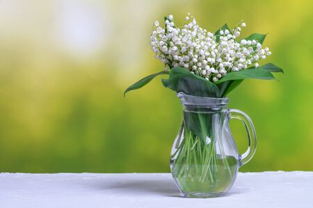 Rural still-life - Lily of the valley in a glass jug, blooming spring flowers, closeup with space for text
