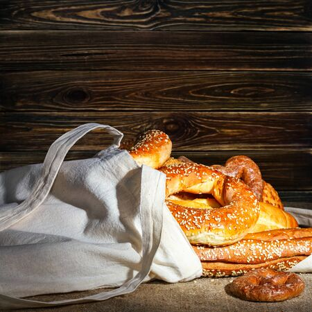 Still-life with fresh bread and bakery in the shopping bag, with space for text