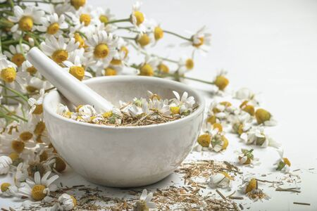 Rural still-life - chamomile crushed in a mortar on the background of a bouquet of daisies, closeup