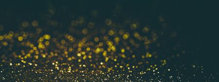 Black with gold glittering background, banner. Sparkle glitter texture with the bokeh and the lights, shiny metal gold foil