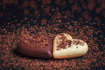 Two heart-shaped chocolates made of milk and white chocolate on the slate board, covered in grated chocolate. Desserts for Valentines Day.