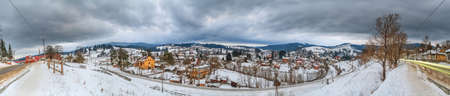 Rural winter landscape, panorama, banner - view of the village Vorokhta with the railway in valley Prut River the Carpathian Mountains, in Ukraine