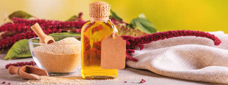 Amaranth oil in a bottle and amaranth grits in a glass bowl with blooming branch amaranth, banner, closeup with selective focus Stock Photo