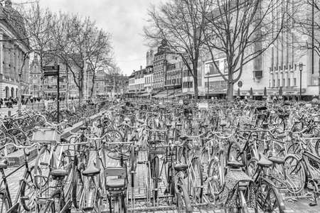 Cityscape on a winter day, in black-and-white color - view of the bike parking in the historic center of Amsterdam, The Netherlands Redakční