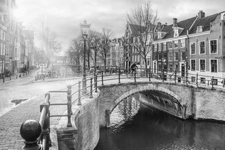Cityscape on a sunny winter day, in black-and-white color - view of the bridge and canal in the historic center of Amsterdam, The Netherlands