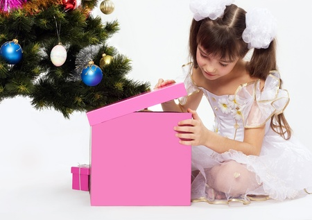 Little smiling girl opening christmas present by a Christmas tree photo
