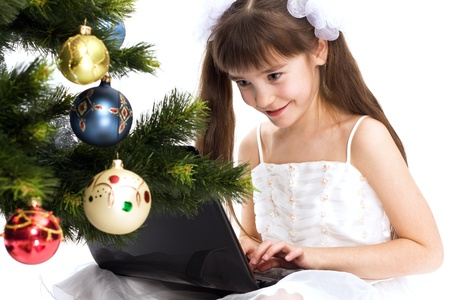 Little smiling girl looks at her laptop computer by a Christmas tree Stock Photo - 11300115