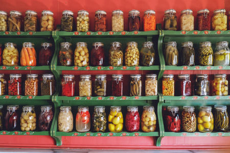 glass jars: collection of glass jars with colorful pickled vegetables Stock Photo