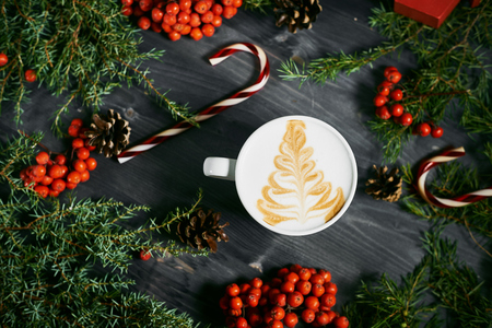 background people: Cup of coffee with a Christmas tree pattern on a wooden Christmas background